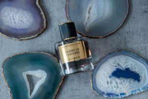 le parfum à la cerise Cherry of Cashmere posé près de pierres