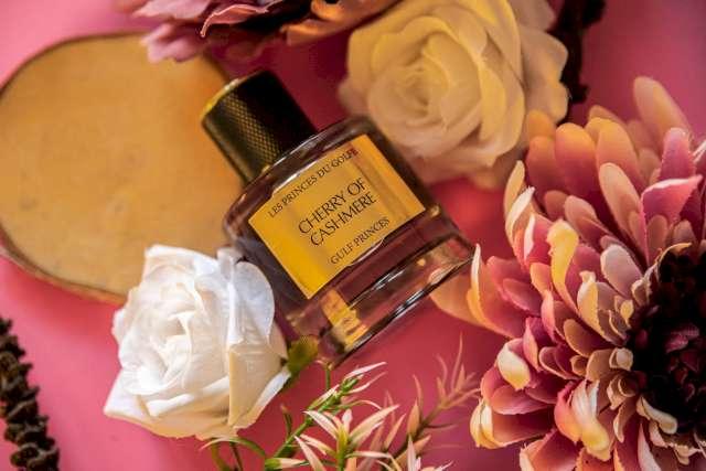 Une photo illustrative du parfum de niche Cherry of Cashmere entouré de 2 fleurs blanches et d'une fleur rose.
