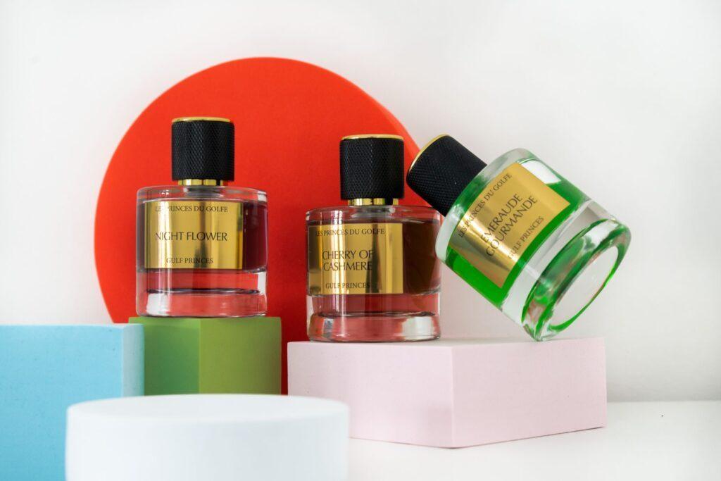 Une photo illustrant trois flacons de parfum de niche. Emeraude Gourmande, Cherry of Cashmere et Night Flower.