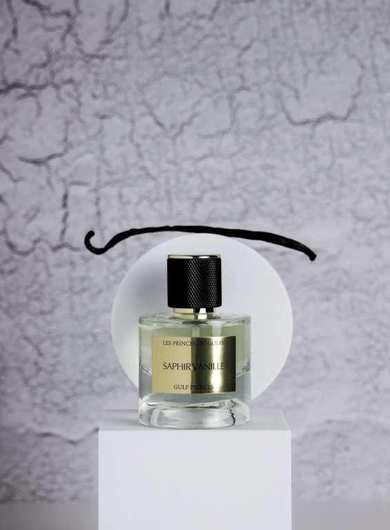 Une photo du parfum saphir vanille sur lequel est posée une gousse de vanille marron.