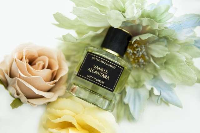 Une photo qui illustre le parfum Vanille Alcantara mis entre trois fleurs. La première fleur à gauche est de couleur beige, la deuxième fleur en bas est de couleur jaune, la troisième fleur en haut est verte.