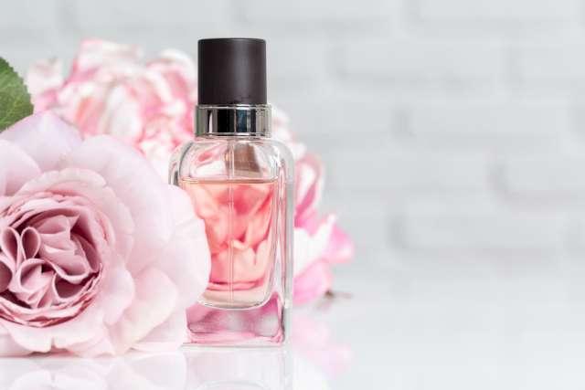 Une photo illustrative d'un flacon de parfum transparent mis a coté d'une fleur de rose. Le fond est flouté, à moitié gris et l'autre moitié est constituée par une deuxième toujours floutée.