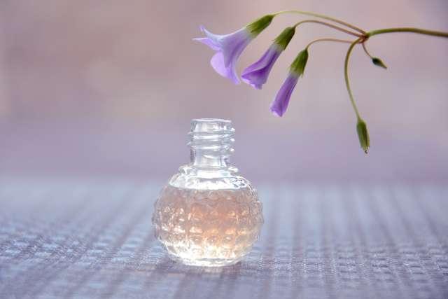 Une photo illustrative d'un flacon de parfum ayant une forme ronde et trois fleurs violette en dessus du flacon.
