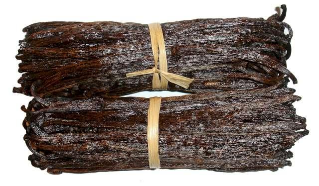 Une photo illustrative de gousses de vanille brunes et prêtes à l'utilisation, attachées par un un petit fil de couleur crème.