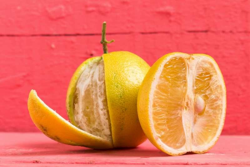 Une photo illustrative de deux fruits de bergamote. La première est coupée à demi et la deuxième est derrière et complète. Une partie de sa peau est enlevée à moitié.