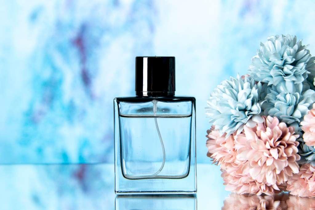 Une photo d'un flacon de parfum simple mis à coté de fleurs roses et bleus sur un fond bleu floutée.